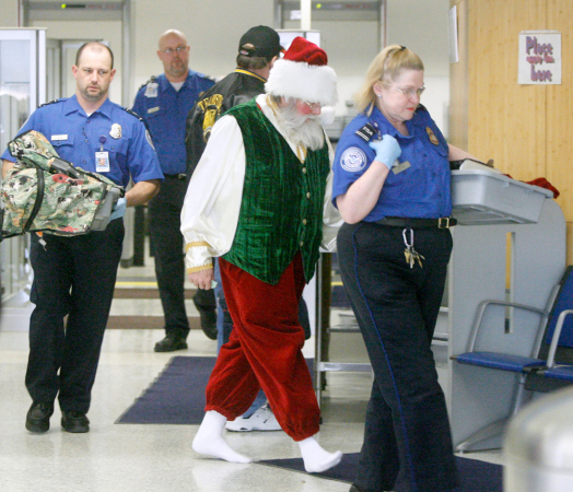 Image: Santa Claus Larry Durian is taken to a private TSA room after passing through metal detectors at the Akron Canton Airport